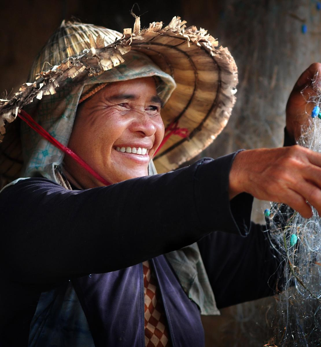 A woman happily dries out a fishing net.