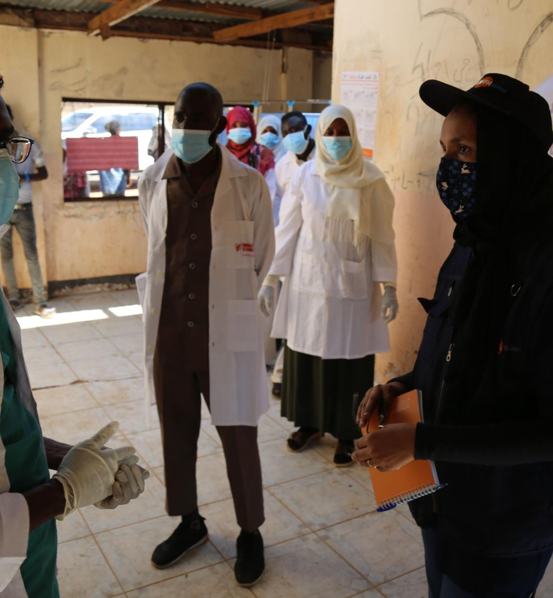 Medical personnel speak to UN staff at the camp medical facility as they wear PPE and social distance.