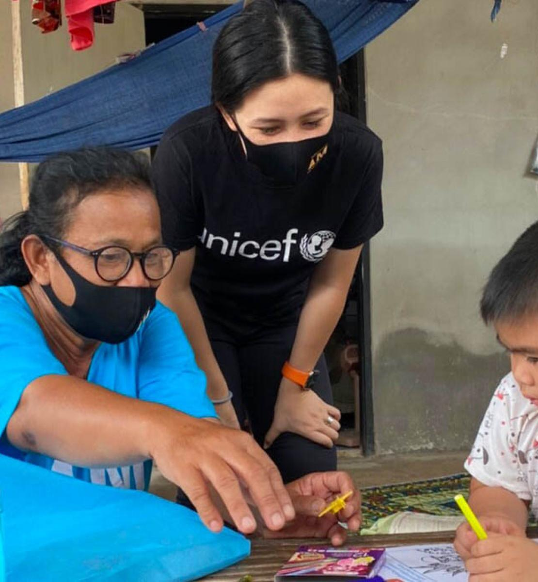 UNICEF volunteer, Rasa Pattikasemkul (centre), interacts with a young boy in a rare face-to-face meeting during the COVID-19 lockdown.