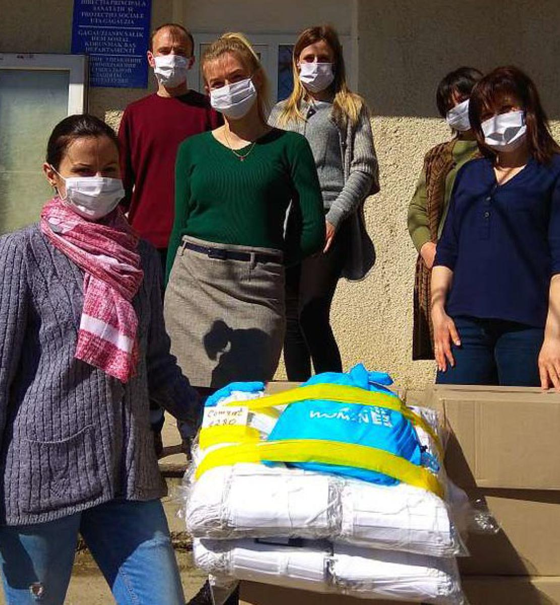 Essential workers and UN personnel stand outside by donated supplies as they wear face masks and social distance.