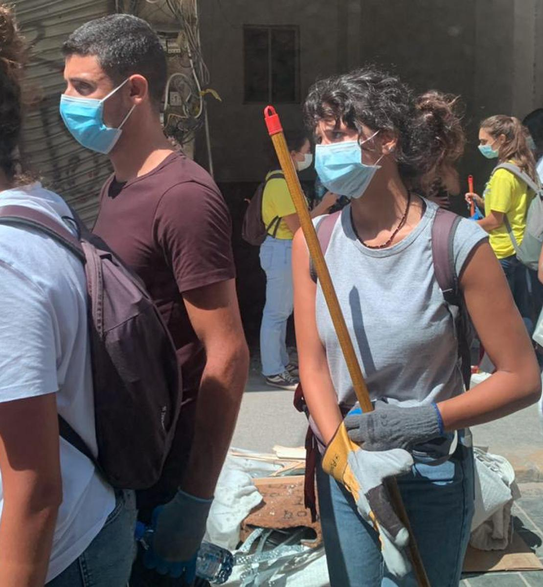 Youth volunteers walk together with equipment and supplies as they wear protective masks.