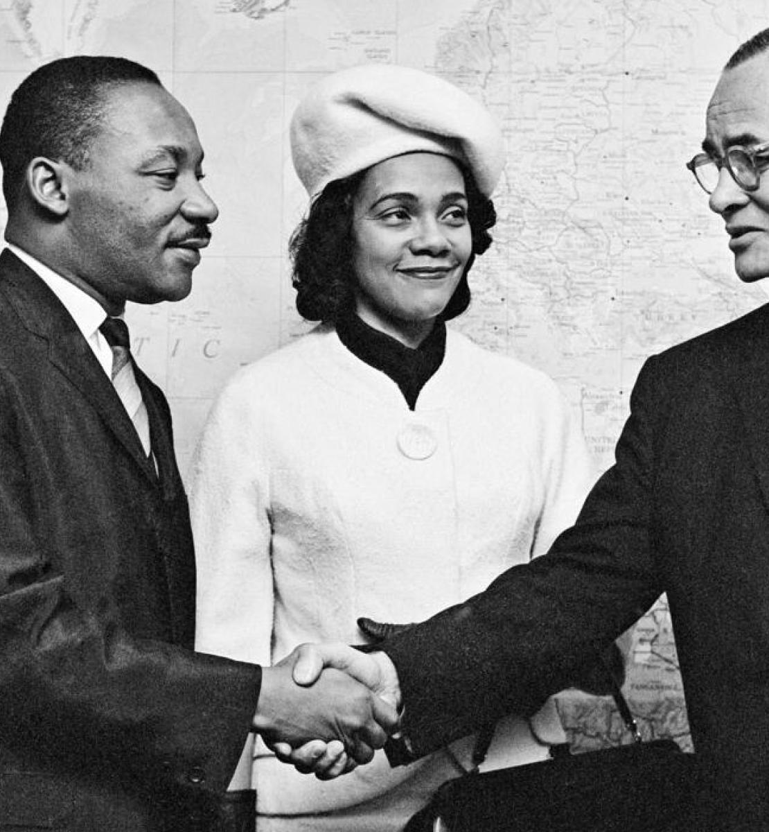 Black and white photo of Dr. Martin Luther King and his wife Coretta Scott King are seen being greeted by Mr. Ralph J. Bunche, UN Under-Secretary for Special Political Affairs in 1964.