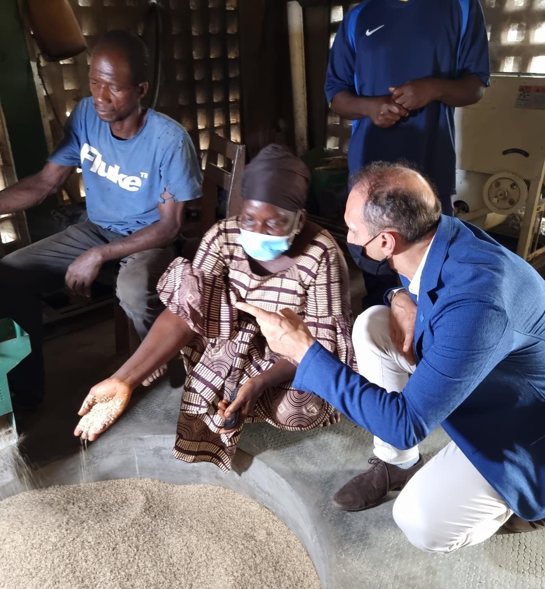 Le Coordonnateur résident Vincent Martin se tient aux côtés d'un leader de la communauté. Tous deux discutent, agenouillés, devant une machine qui déverse des grains dans un grand récipient rond.
