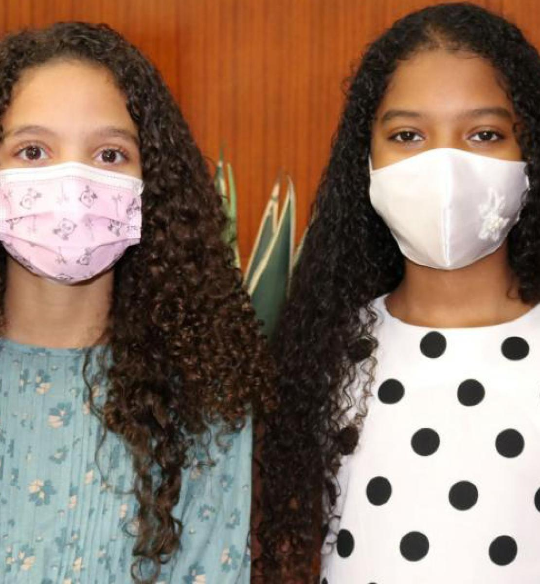 Anyah Spencer Maia and Victoria Roberts Gonçalves Gomes, age 10 stand side-by-side facing the camera wearing face masks.