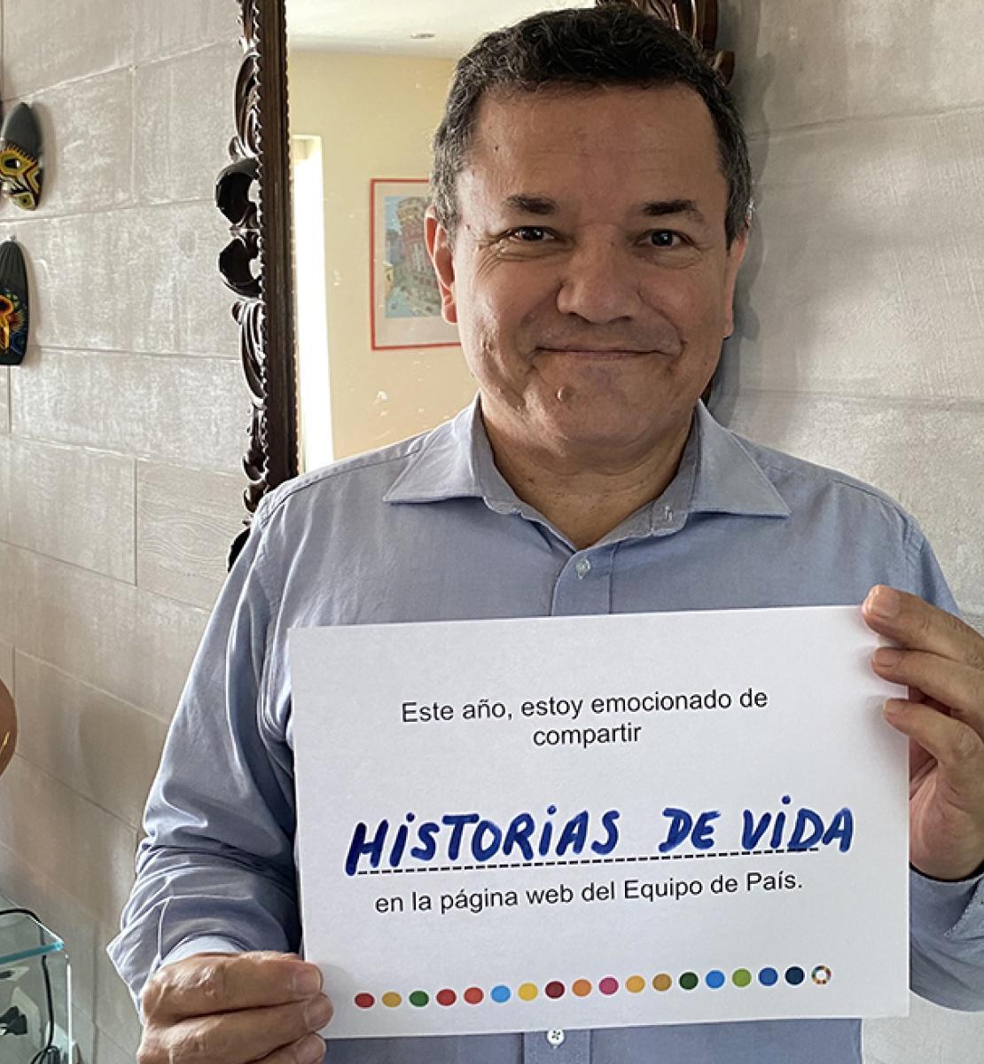Un hombre sonríe dulcemente a la cámara mientras sostiene un pequeño letrero que comparte su visión de futuro sobre el sitio web, en español.