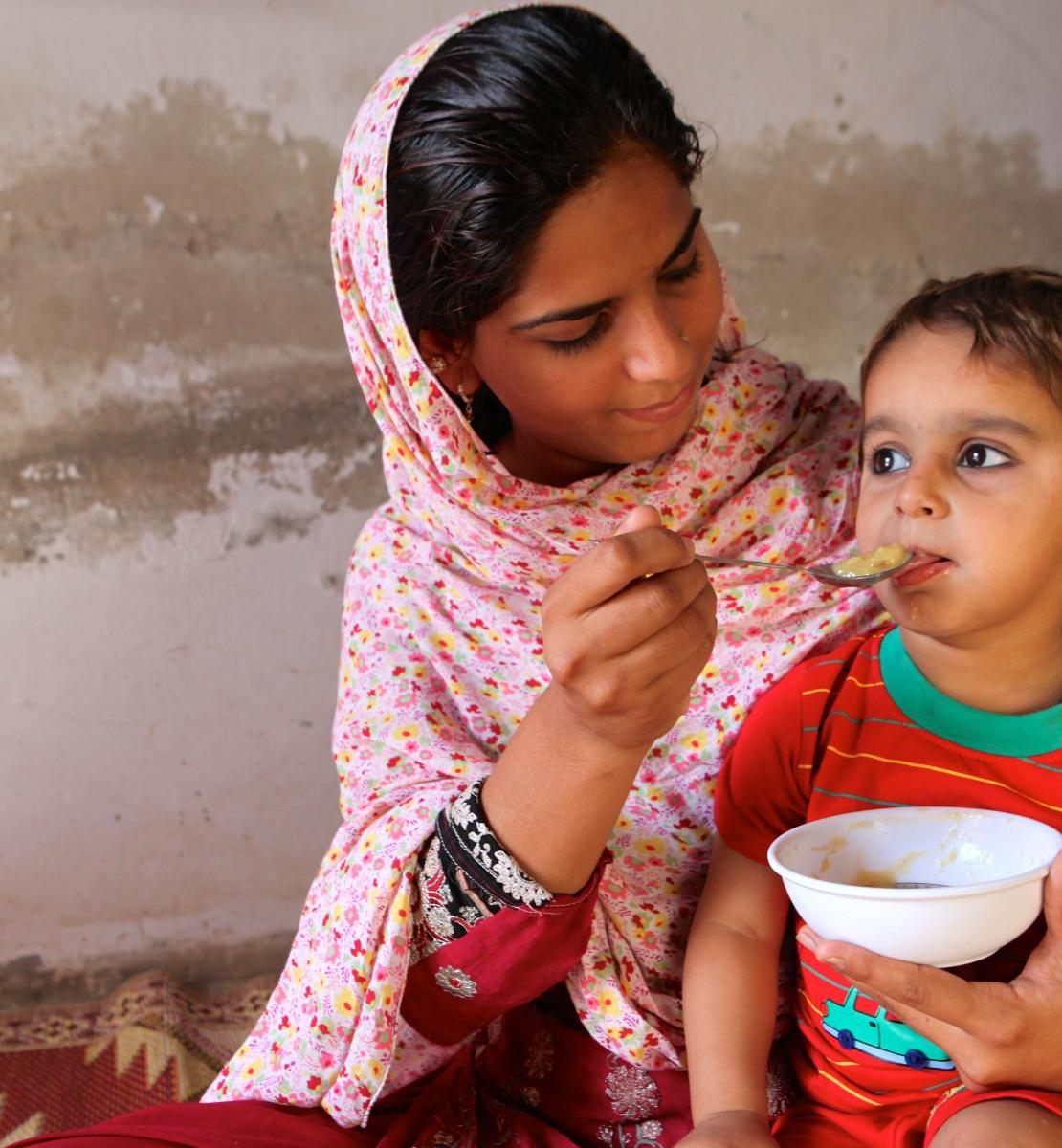 A young woman holds a child in her lap while she feeds him from a bowl.