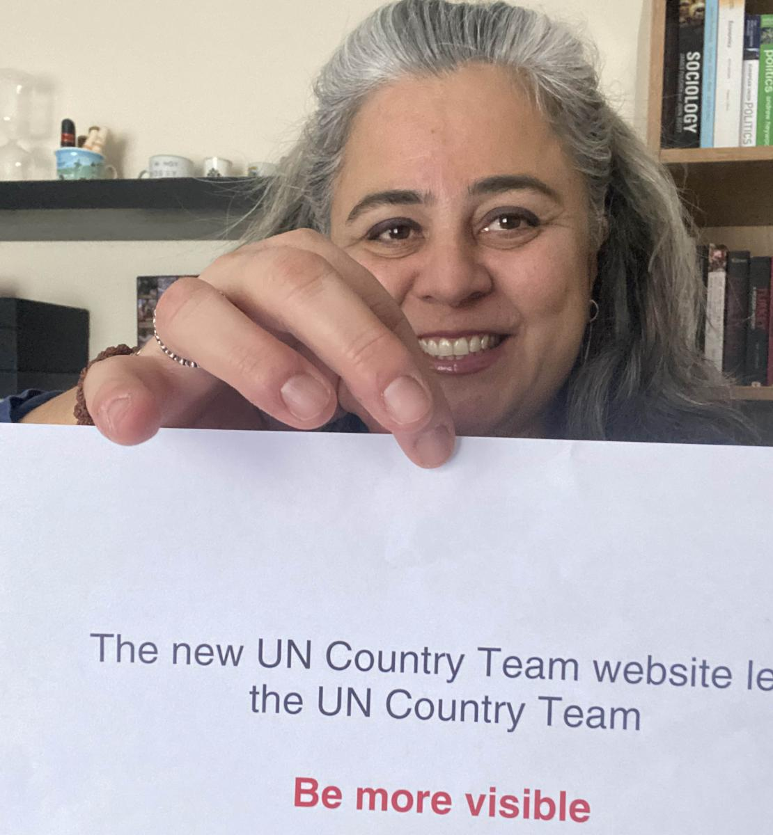 "A woman smiles cheerfully at the camera as she holds a sign that reads ""The new UN Country Team websites lets the UN Country Team BE MORE VISIBLE"""
