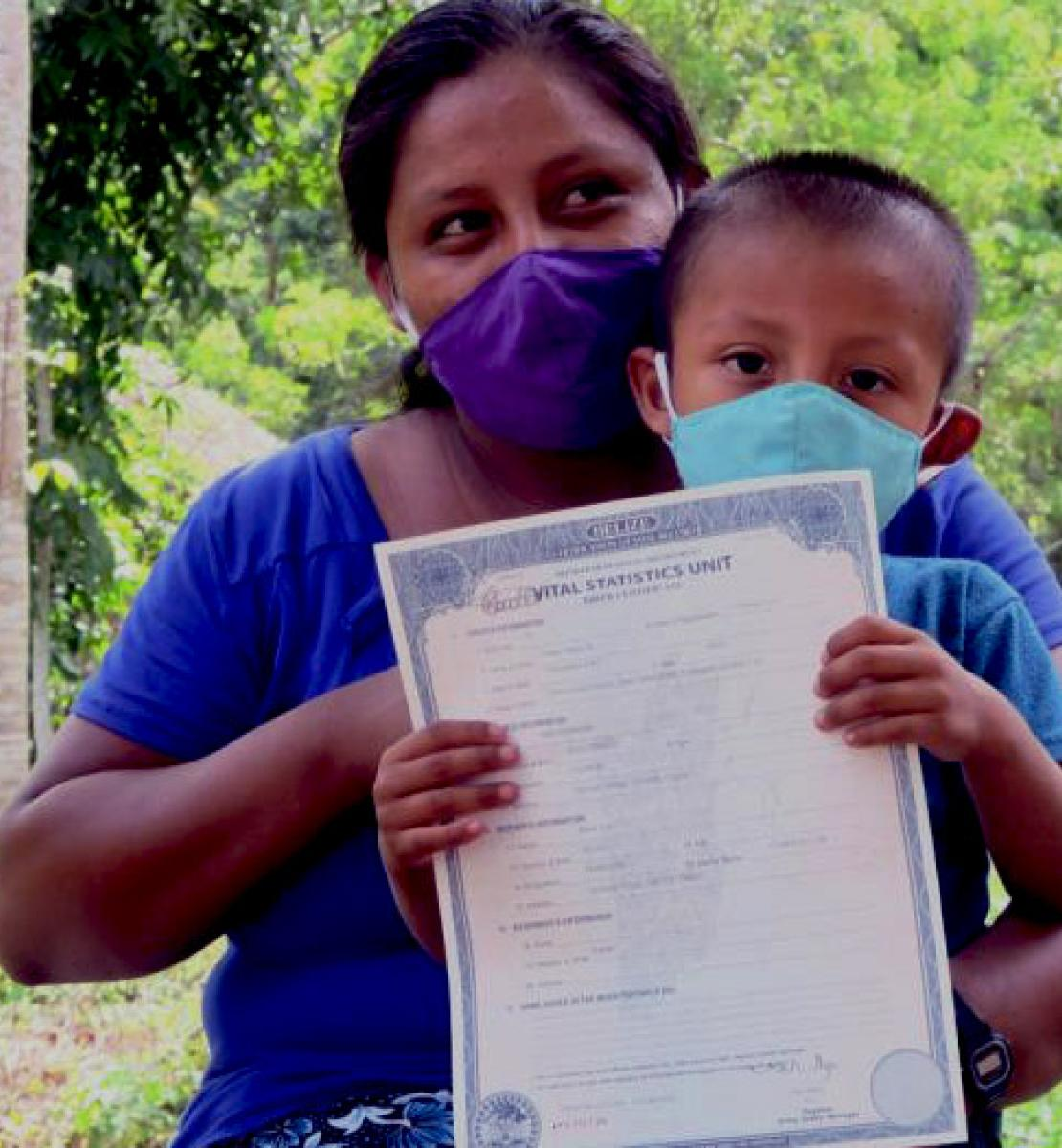 A mother wearing a protective face mask gazes to the left of the camera as she holds her son, also wearing a face covering. He proudly holds up his registration.