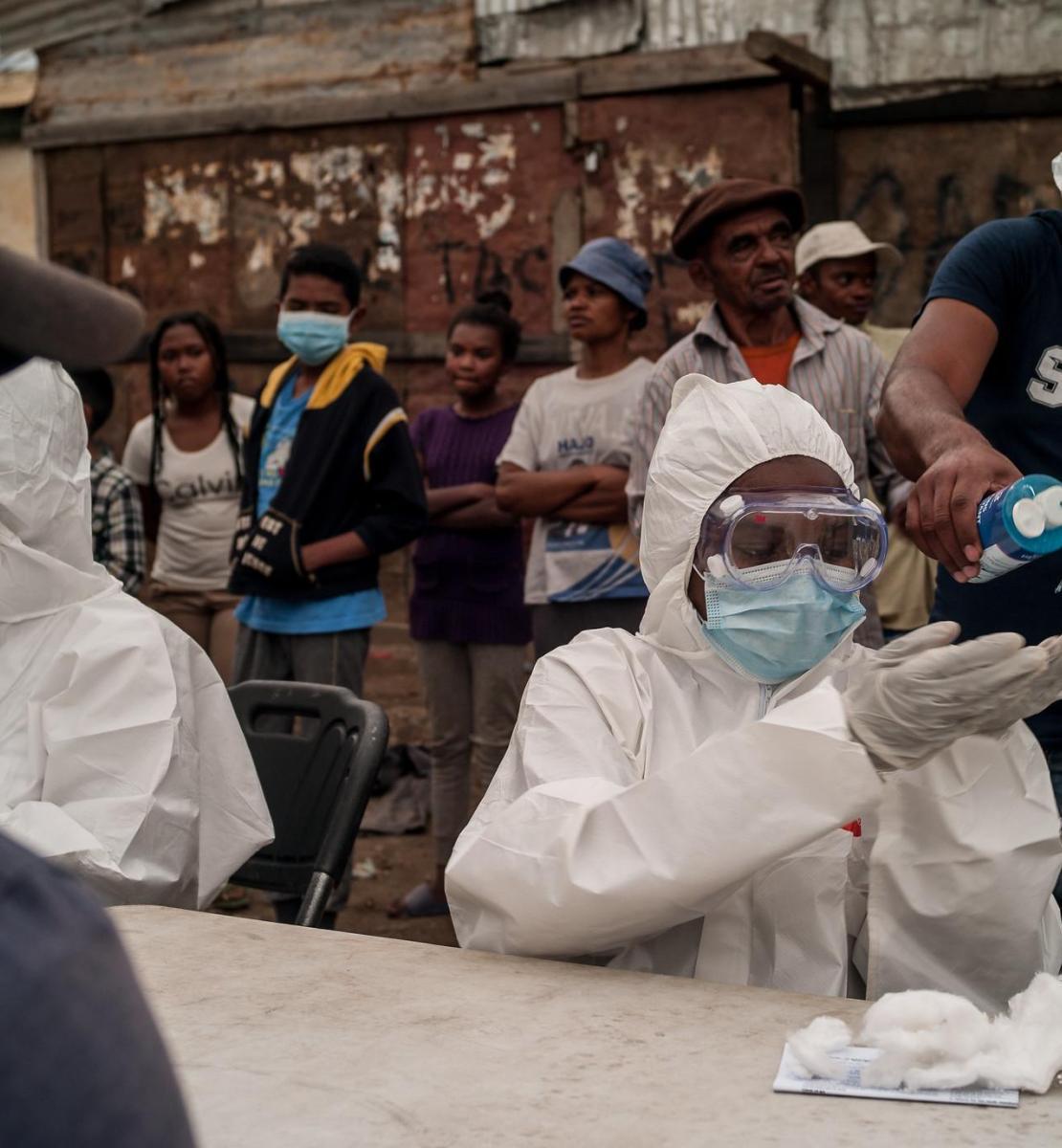 Des personnes patientent derrière une table où sont assis des travailleurs de la santé portant des équipements de protection individuelle de la tête aux pieds. Un homme verse du désinfectant dans les mains d'un des travailleurs de la santé, tandis qu'un autre est assis en face.