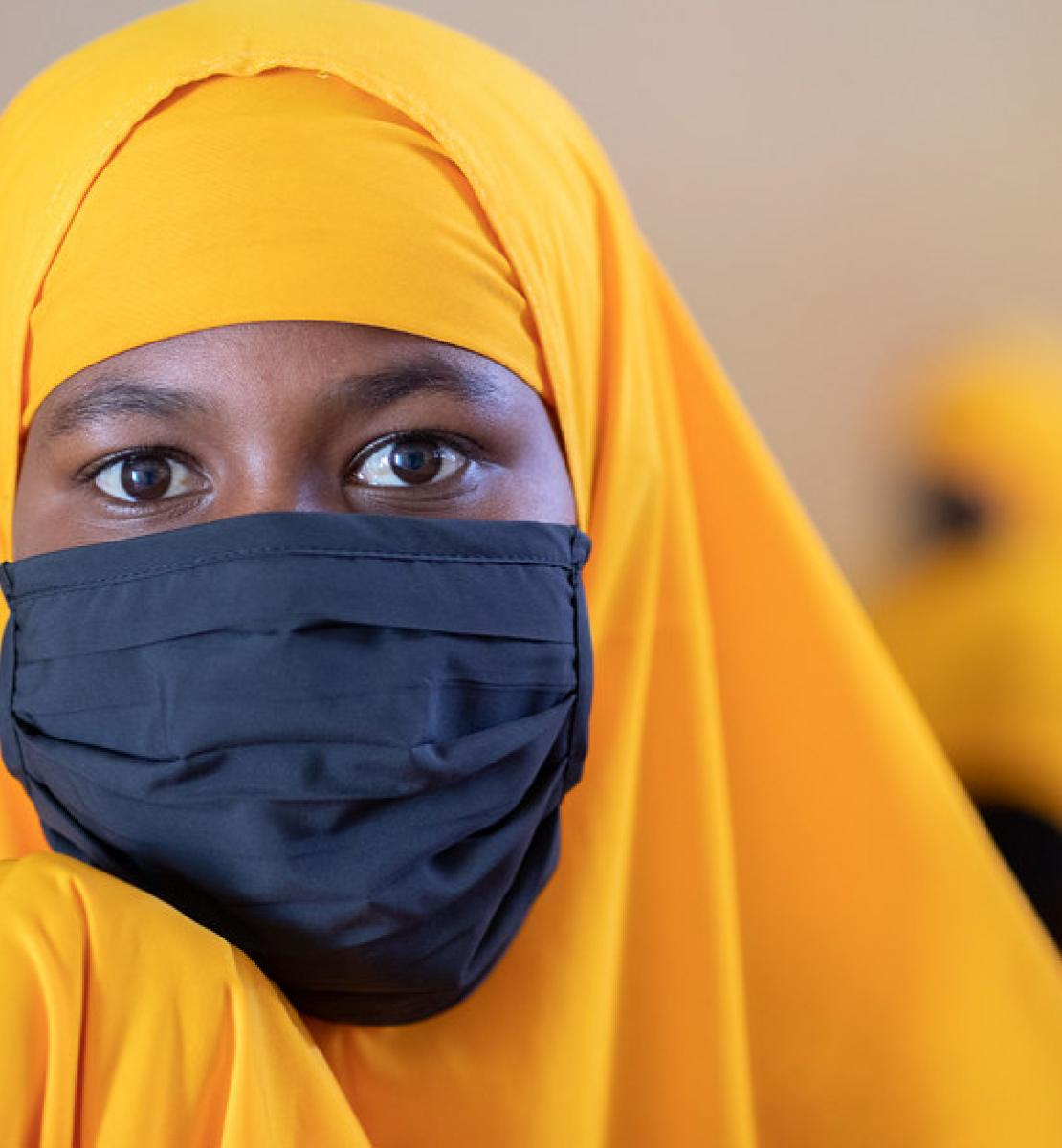 A young adolescent girl wearing a yellow headdress and black mask looks strikingly at the camera.
