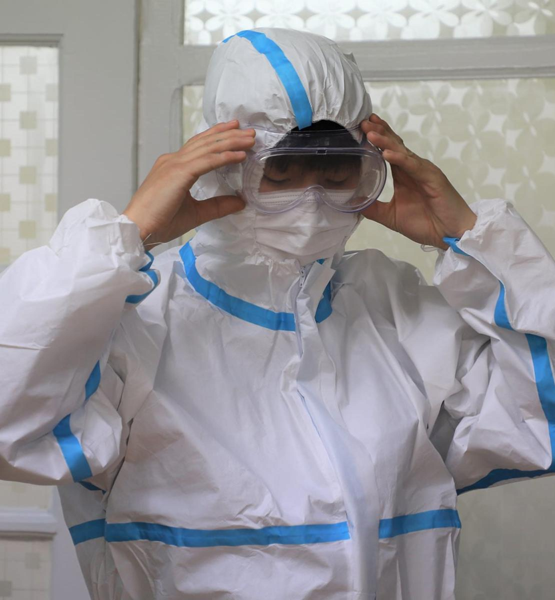 A healthcare worker tries on head-to-toe personal protective equipment.