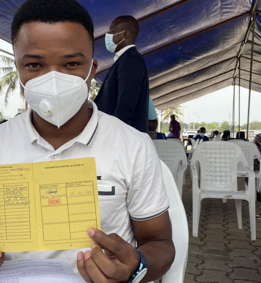 A man in a white shirt and white face mask holds up a yellow COVID-19 vaccination card.