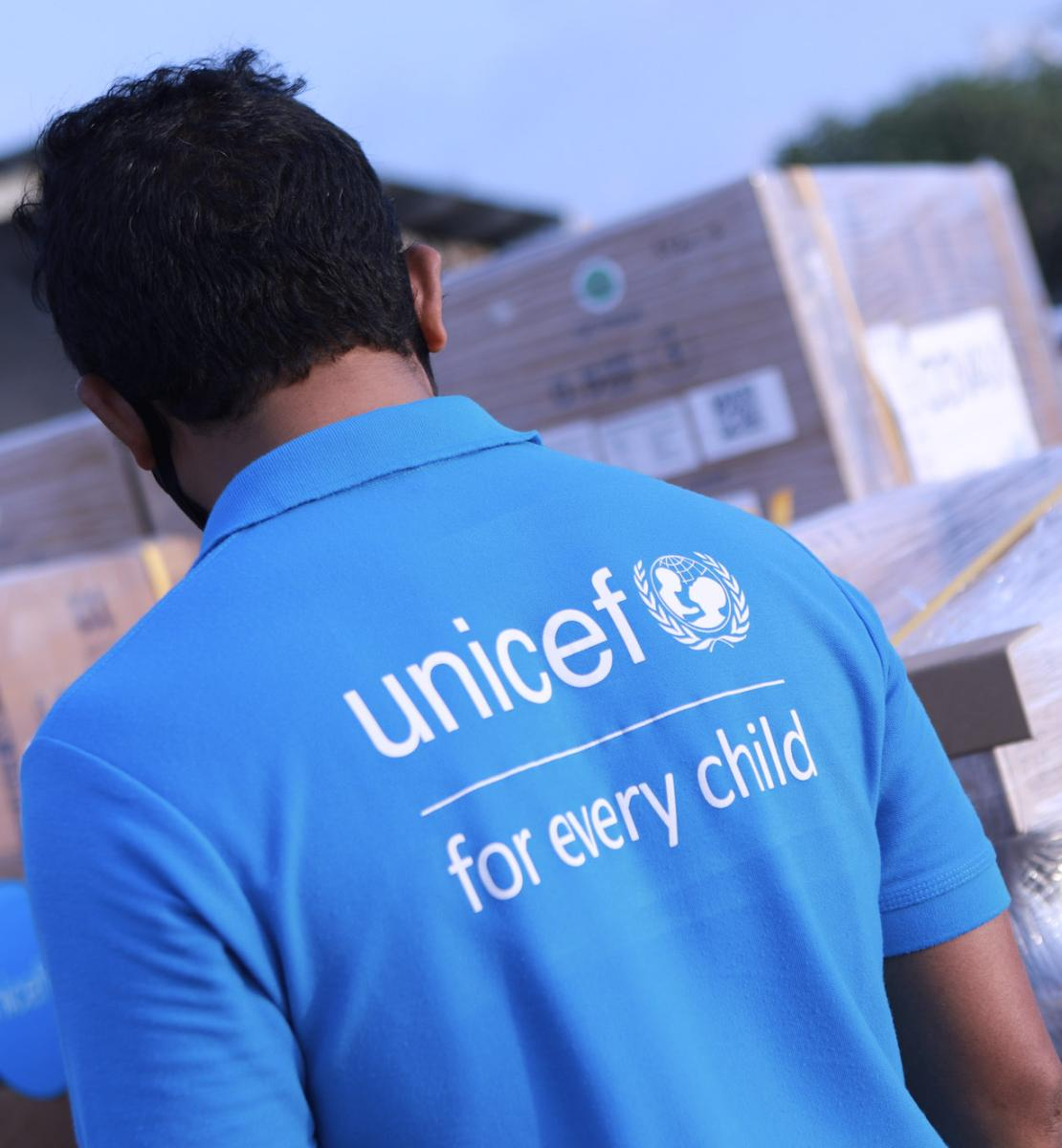 A man wearing a light blue UNICEF shirt looks over the delivery of vaccines wrapped in wrapping paper.