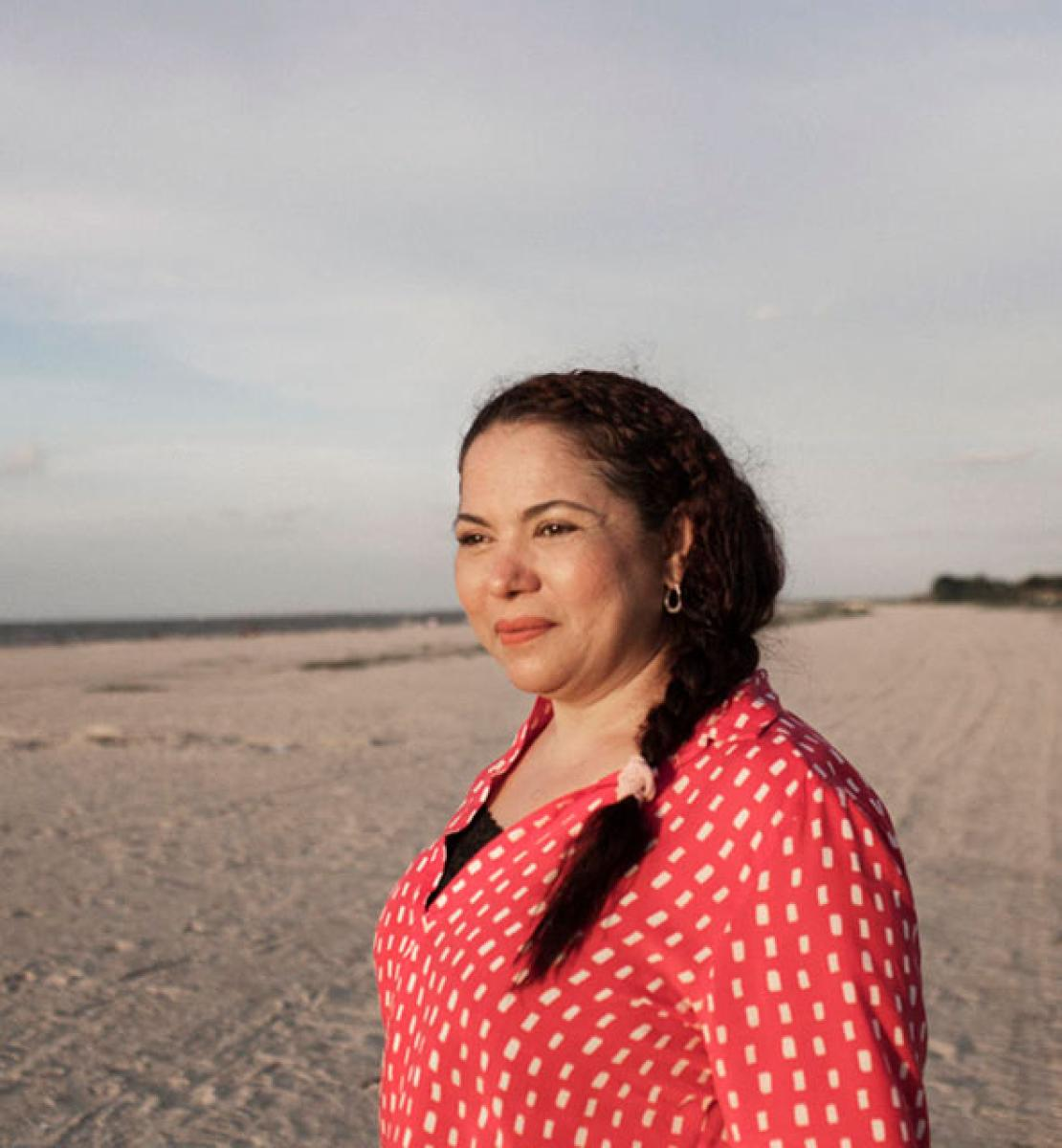 Woman in a red shirt looks out into the distance at a sandy location.