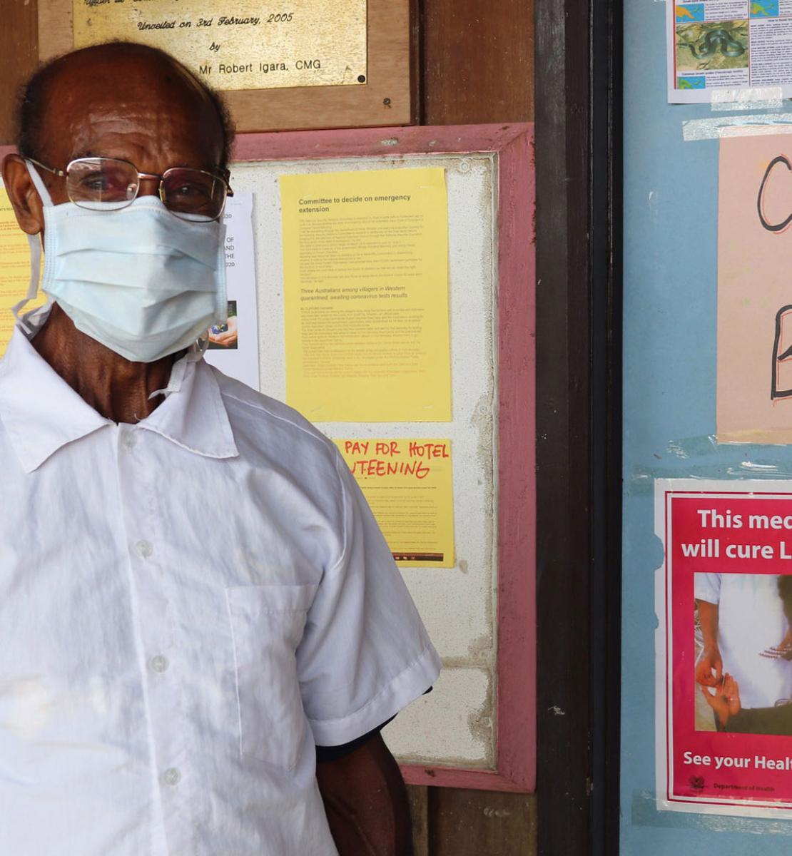 Un hombre con una camisa blanca y una máscara blanca se encuentra delante de un tablón de anuncios con información sobre la COVID-19.