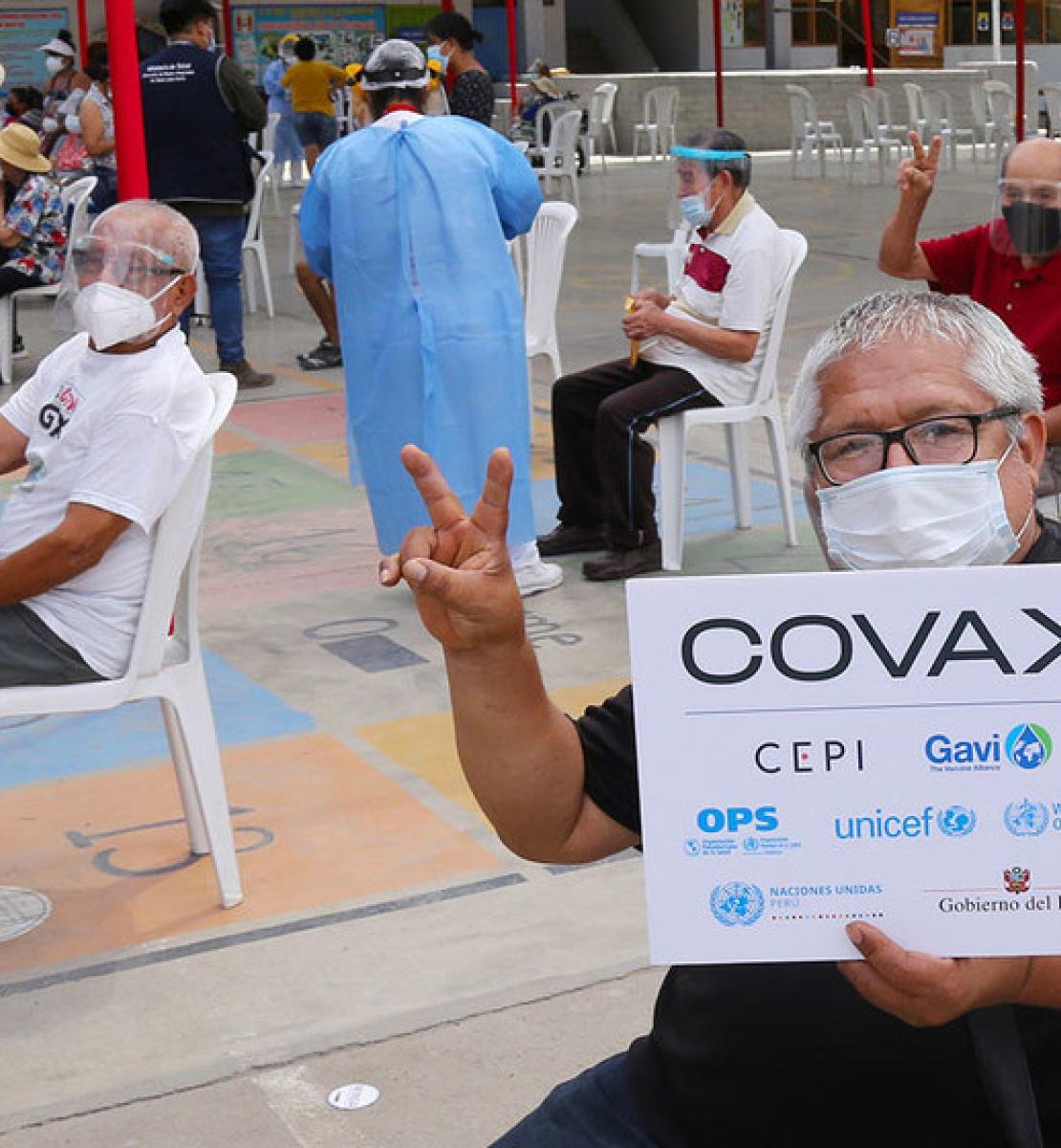 """Des personnes d'un certain âge sont assises sur des chaises blanches au milieu d'une grande esplanade. Elles sont distantes les unes des autres, portent des masques et pour certaines des visières de protection, en attendant les consignes des agents de santé. Parmi elles, un homme, au premier plan de l'image, face caméra, tient un panneau où l'on peut lire « COVAX » et le nom d'organismes partenaires. D'autres personnes autour de lieu font le signe """"V"""" de la main pour signifier qu'elles se sont fait vaciner."""