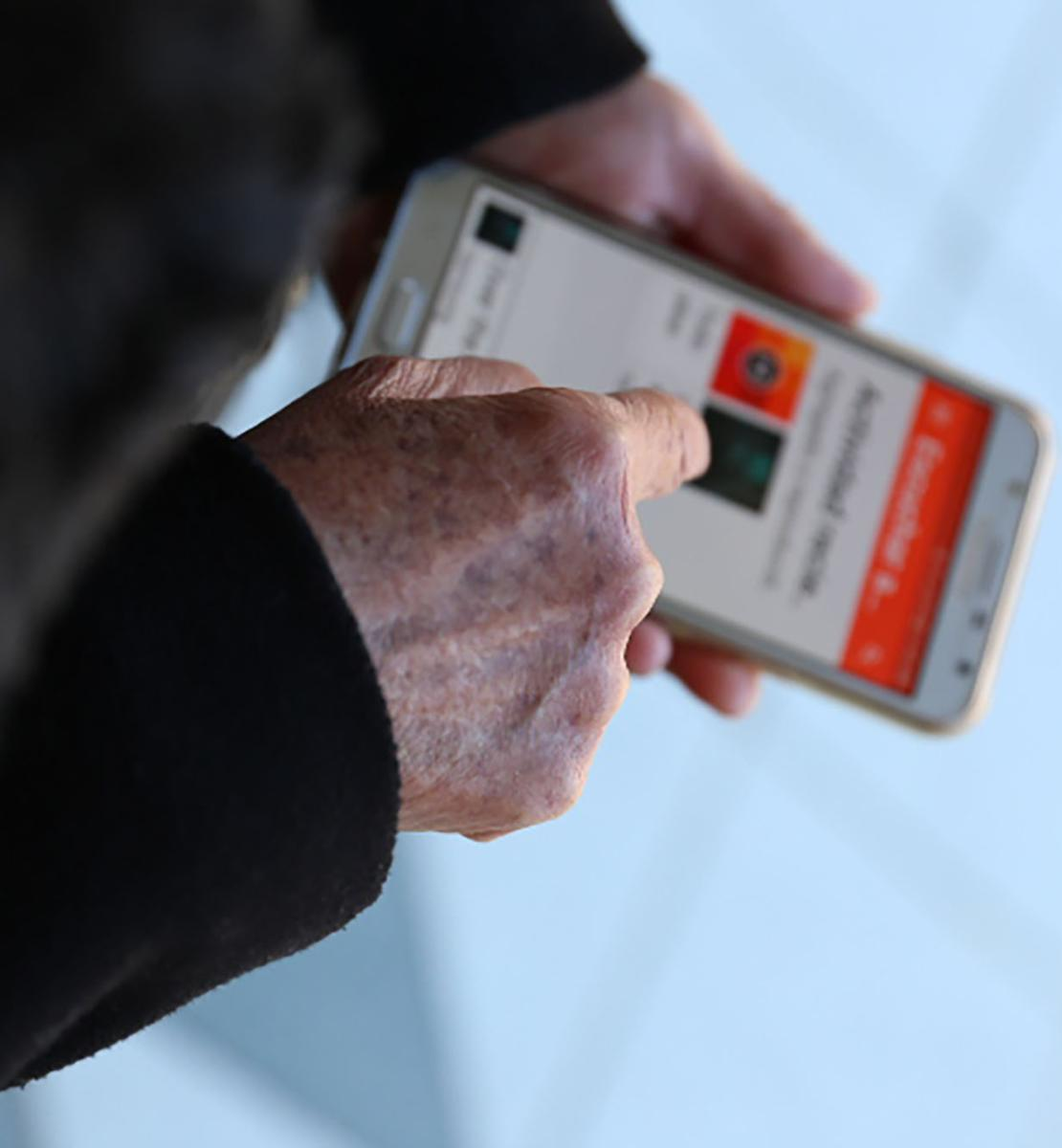 Gros plan sur les mains d'une personne utilisant une application mobile sur son téléphone portable.