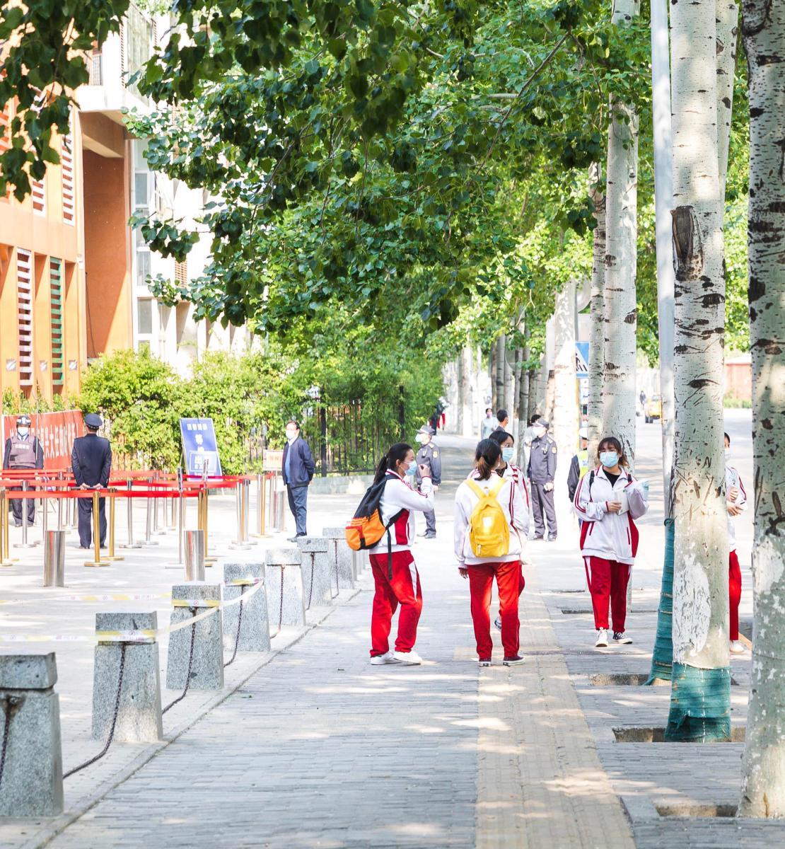 De jeunes collégiennes portant un masque de protection se tiennent debout devant l'entrée d'un établissement scolaire, au milieu d'une contre-allée bordée de grands arbres. A droite de l'image, on aperçoit une grande avenue et à gauche, quelques adultes se tenant juste devant la porte de l'établissement.