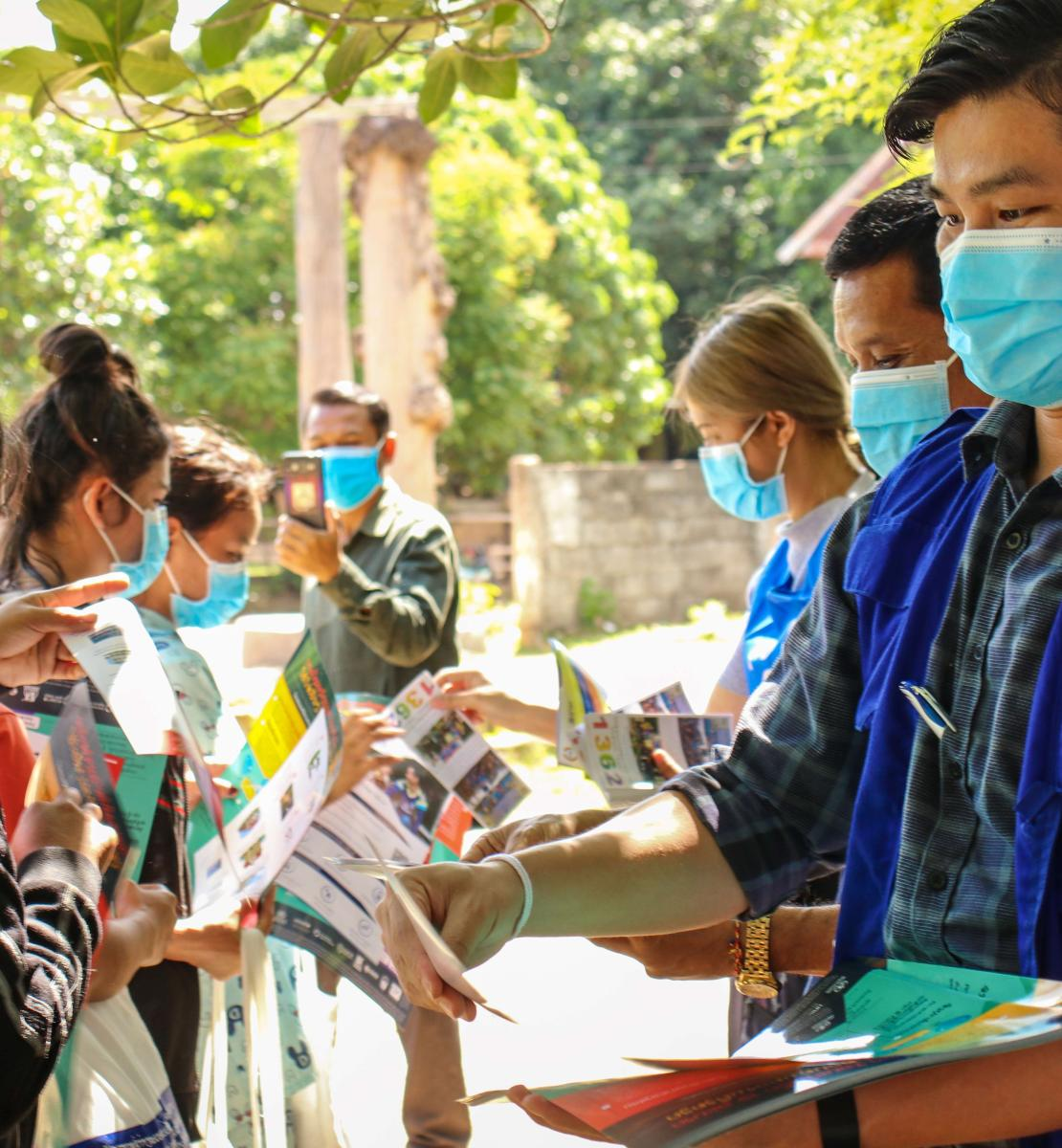 Plusieurs membres du personnel de l'OIM portant des vestes bleues et des masques de protection distribuent des brochures d'information à un groupe de jeunes femmes qui portent elles aussi des masques de protection.
