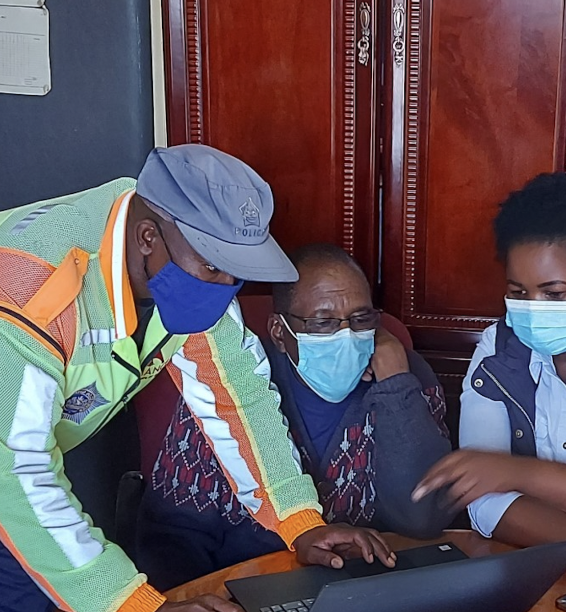 Un hombre con mascarilla y sombrero se inclina sobre dos personas para ayudarles en una computadora.