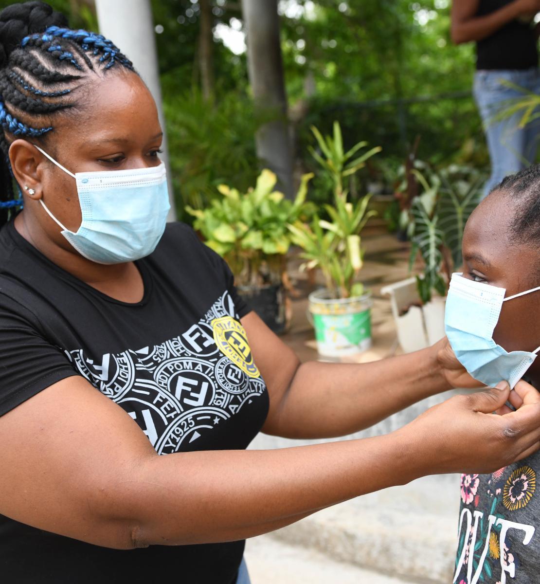 Dans une cours extérieure bordée d'arbustes, une mère ajuste le masque de protection de sa fille, une élève de l'école primaire de Little Bay. Little Bay est une commune principalement composée de pêcheurs située à Westmoreland, à l'extrémité ouest de l'île de la Jamaïque.