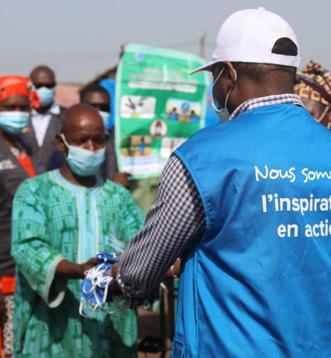 Un Volontaire des Nations Unies portant une casquette blanche et un gilet bleu sur lequel on peut lire « Nous sommes l'inspiration en action » remet plusieurs masques à un homme. Plusieurs personnes se tiennent derrière l'homme qui reçoit les masques. Toutes les personnes apparaissant sur cette photo portent des masques de protection.