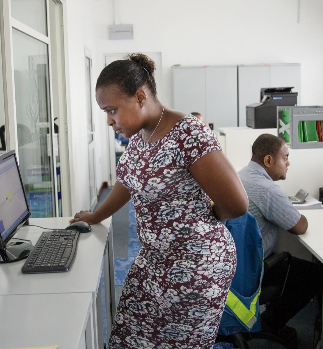 Dans un bureau d'entreprise, une femme vêtue d'une robe travaille, debout, sur un ordinateur, tandis qu'un homme est assis à un bureau, à quelques pas, devant son propre ordinateur.