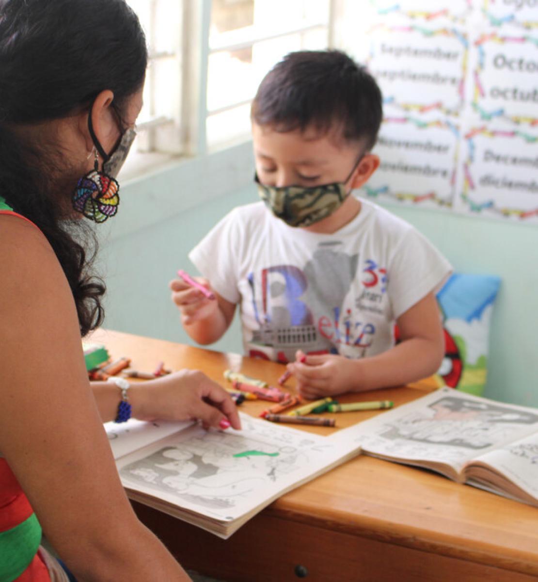 Une femme et un enfant portant des masques de protection sont assis à une table en bois l'un en face de l'autre et regardent des livres de coloriage.