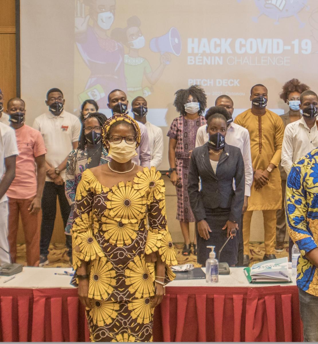 """Un grand groupe de personnes composé de femmes et d'hommes portant des masques de protection se tiennent debout dans une grande salle, face à la caméra, devant un grand écran sur lequel sont projetés les mots """"Hack COVID-19""""."""