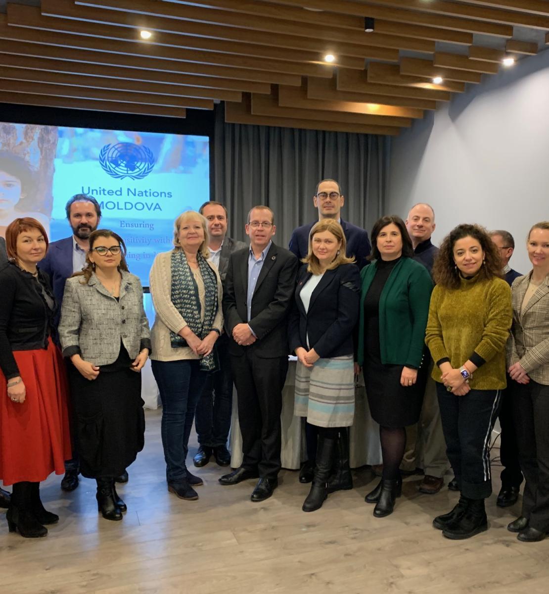 Des femmes et des hommes se tiennent debout dans une salle, face caméra, en souriant. On aperçoit en arrière-plan le logo des Nations Unies en Moldova projeté sur un écran.