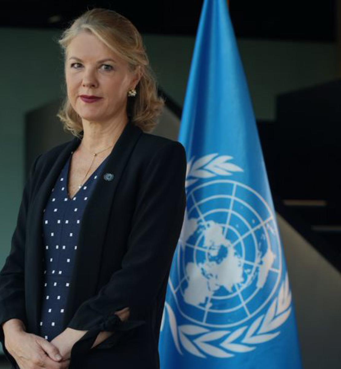 La nouvelle Coordonnatrice résidente des Nations Unies au Brésil, Silvia Rucks, se tient debout devant le drapeau de l'ONU, face caméra.