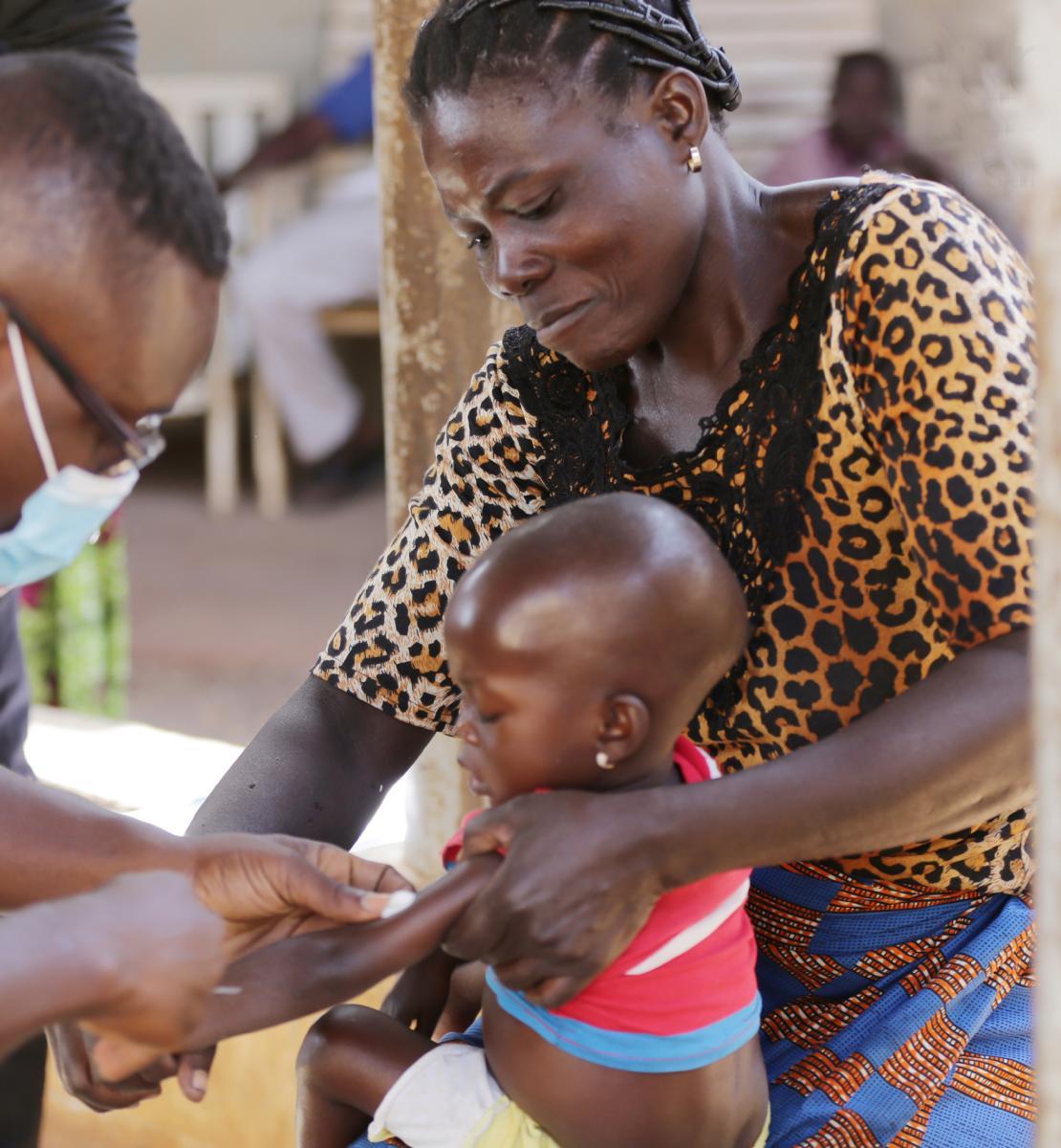 Une mère tient une fillette sur ses genoux. En homme portant un masque chirurgical se penche sur la petite fille pour lui injecter un traitement dans le bras.