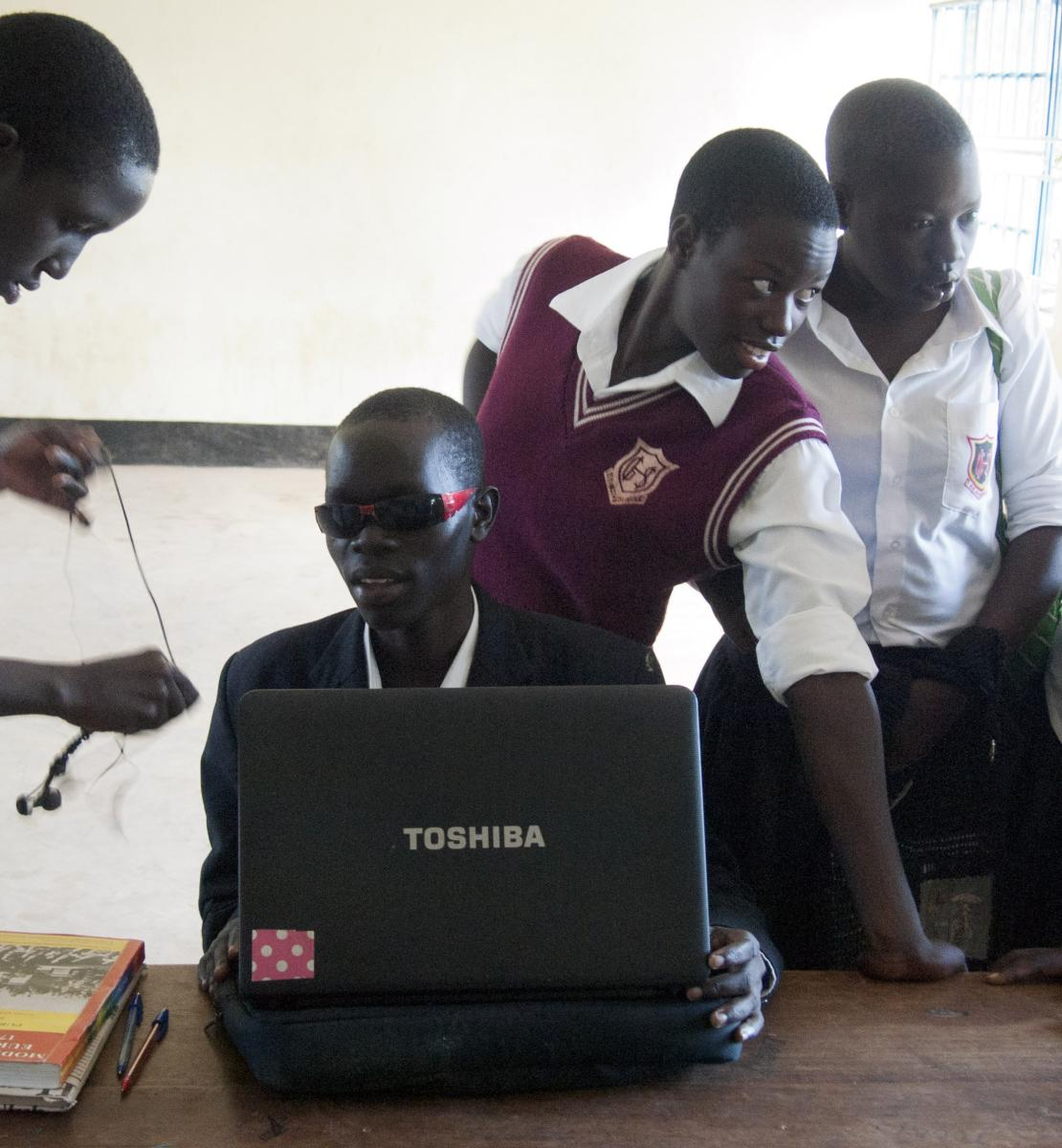 Denis Komakech, 17, who is a blind student, sits with his classmates as he sets up his laptop at Gulu High School, in Northern Uganda.