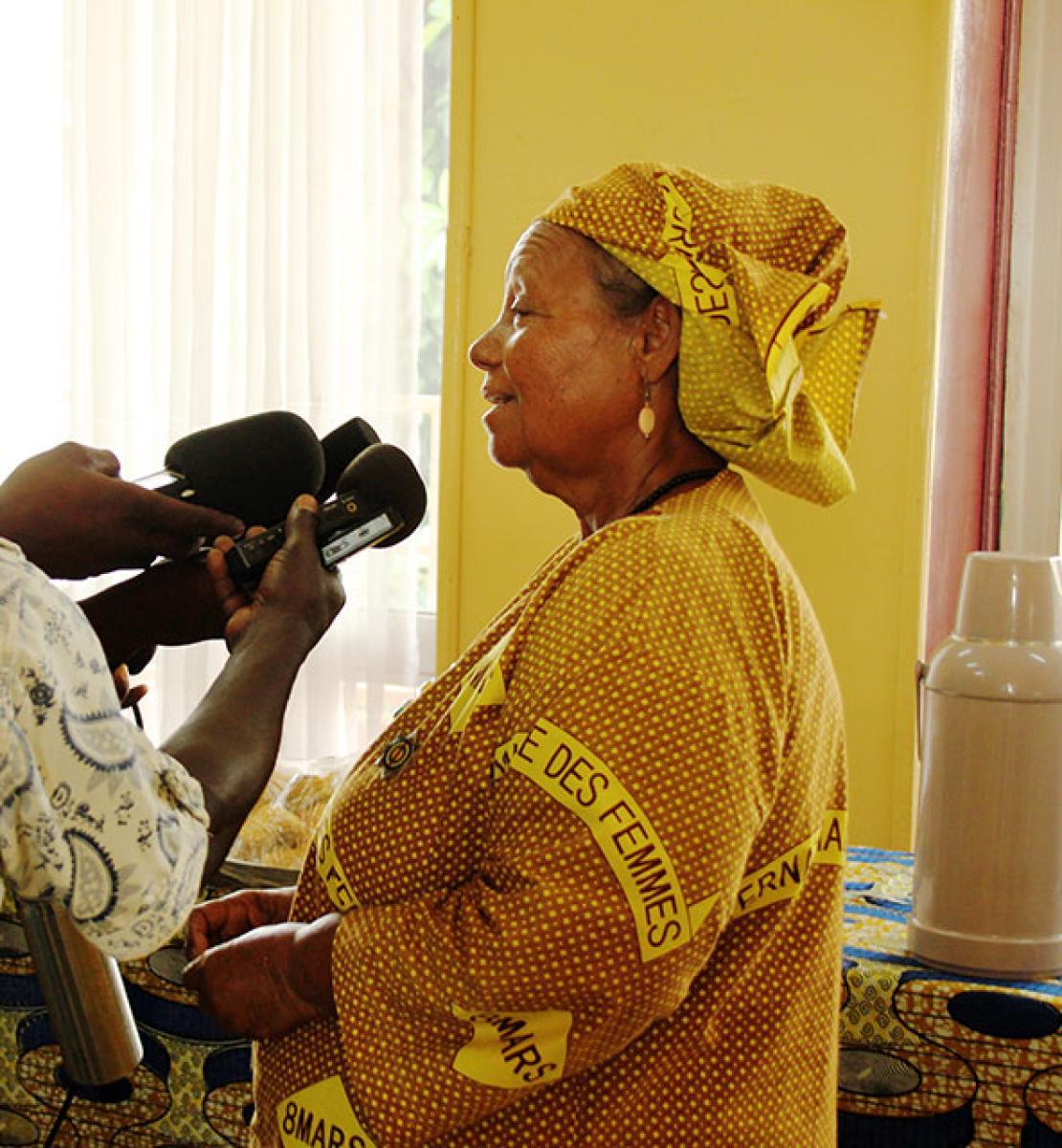 Une femme de la République centrafricaine vêtue d'une robe traditionnelle s'exprime au micro de plusieurs journalistes venus l'interviewer.