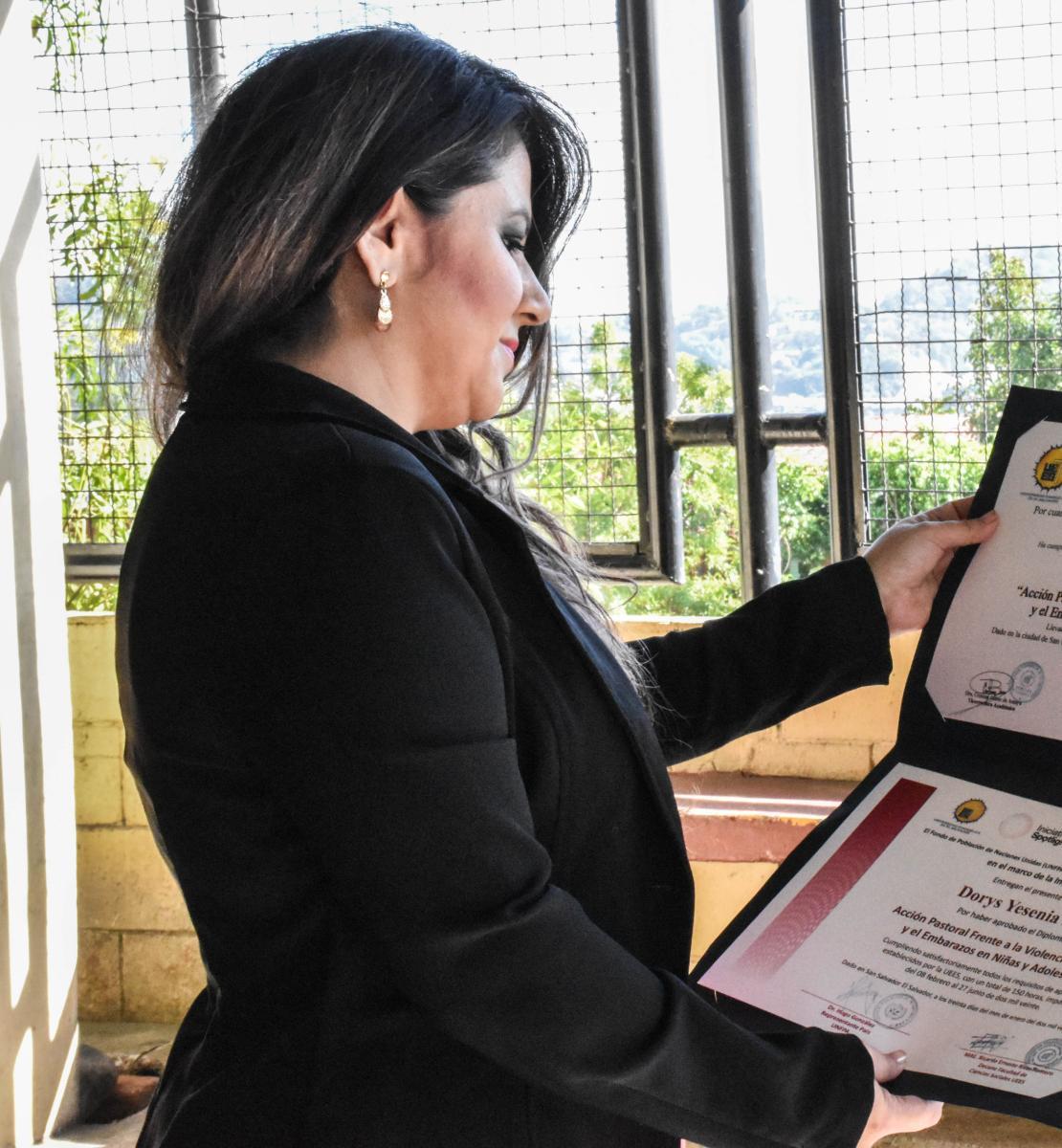 Une femme aux cheveux noirs portant une veste noire regarde son diplôme.