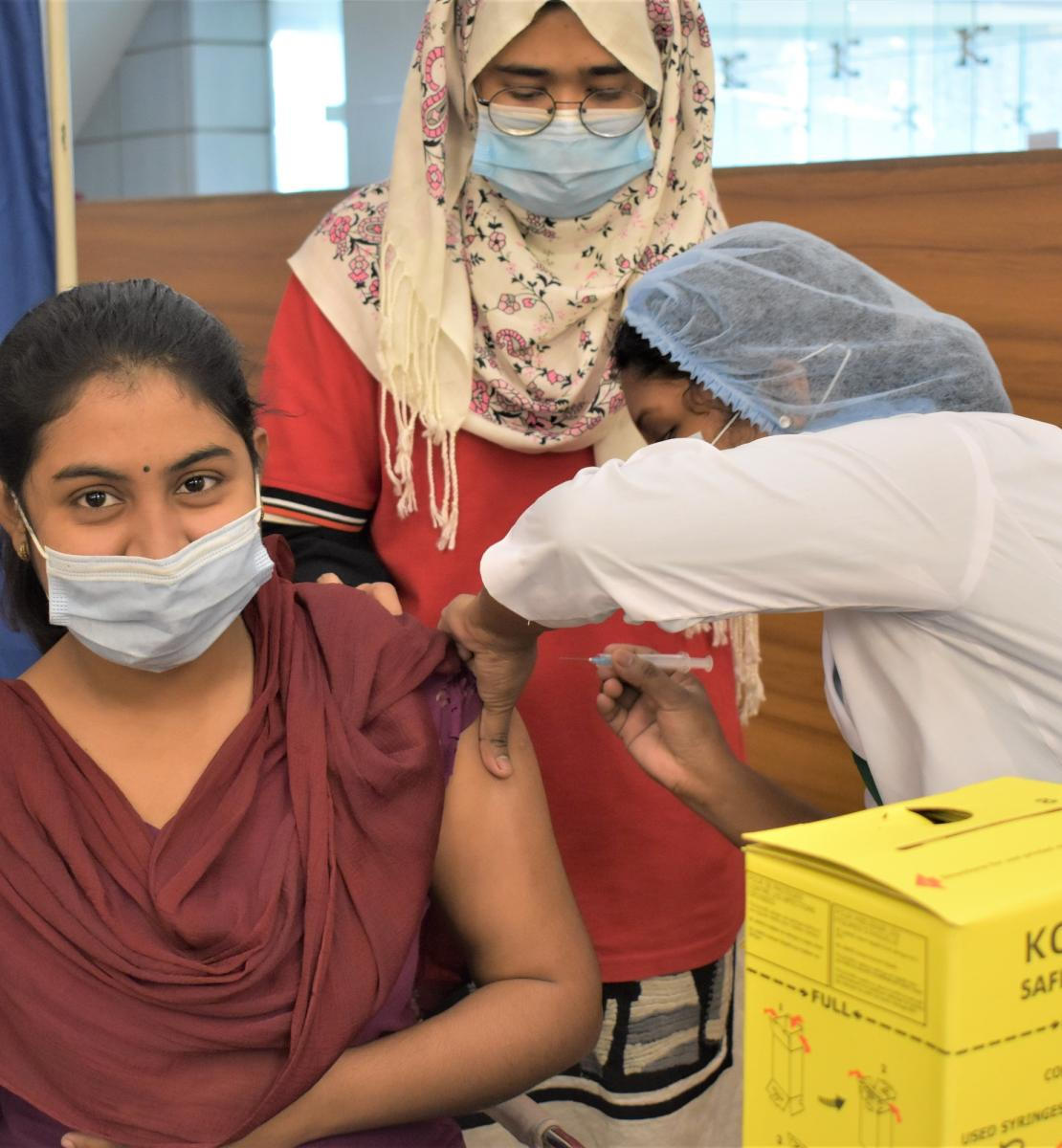 Une jeune femme se fait vacciner contre la COVID-19 en faisant avec les doigts le signe « V », pour « Vaccin ». Une femme portant une blouse blanche et une charlotte bleue lui administre le vaccin. Une troisième femme portant un foulard se tient debout en arrière-plan. Les trois femmes portent un masque de protection.