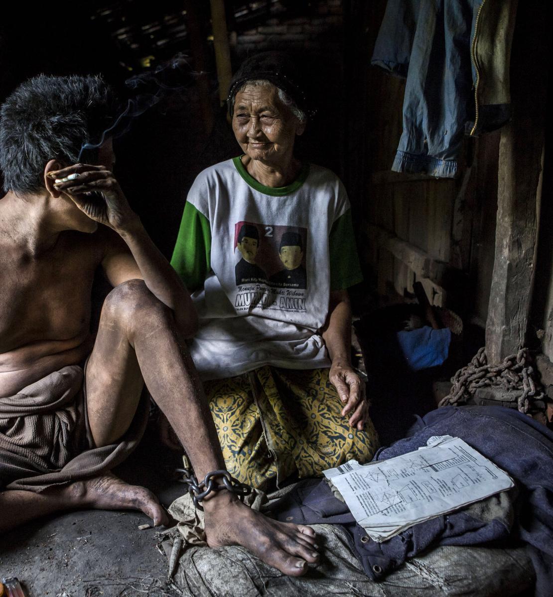 Una mujer y un hombre se miran mientras están sentados en el suelo. El hombre tiene grilletes alrededor de las piernas y está fumando un cigarrillo.