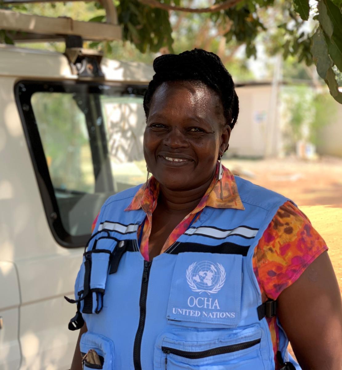 Une femme portant un gilet bleu clair de l'OCHA, le Bureau des Nations Unies pour la coordination des affaires humanitaire, sourit à la caméra.