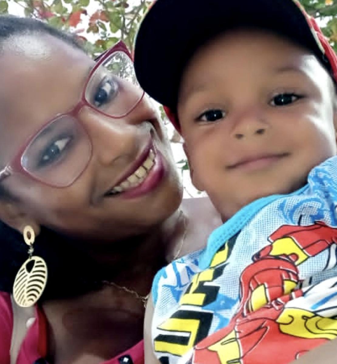 Gros plan sur une femme portant des lunettes, souriant à la caméra et tenant un jeune enfant dans les bras. L'enfant porte une casquette et sourit lui aussi à la caméra.