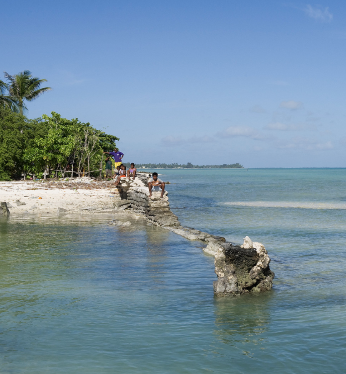 An image of the ocean and several people standing on an island on a sunny day.