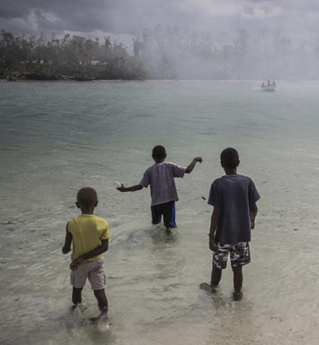 Trois enfants se tiennent debout dans un plan d'eau, dos à la caméra et regardent un bateau s'éloigner.