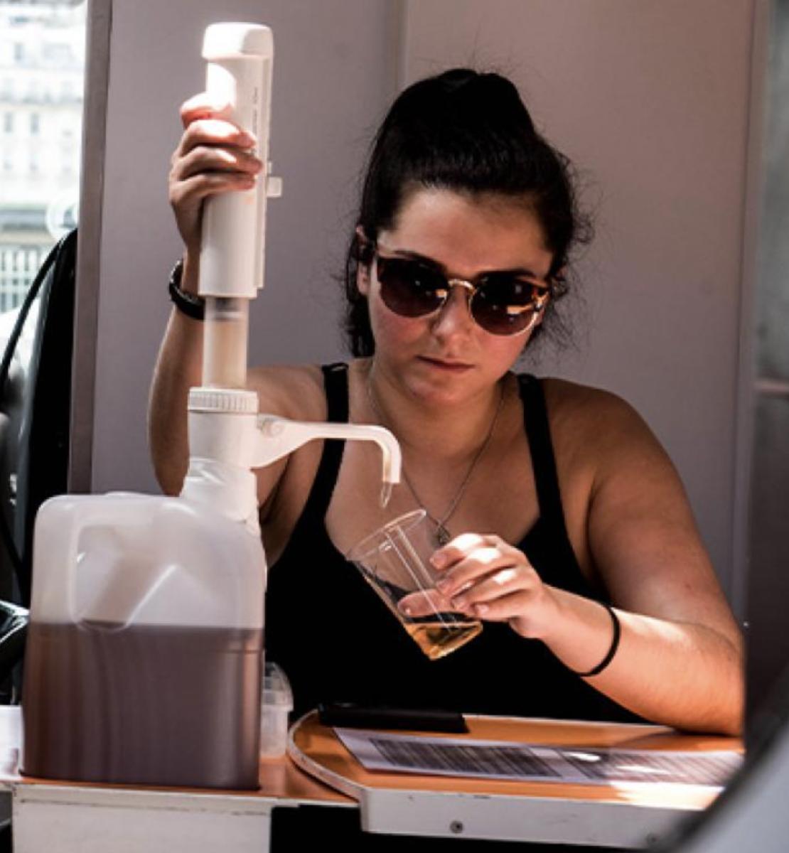 Una mujer con gafas oscuras de sol está sentada en una mesa vertiendo un líquido amarillo-marrón en una taza.