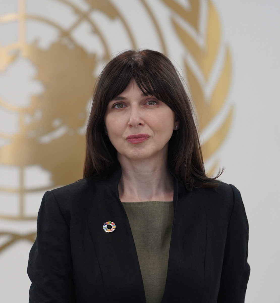 A woman, standing in front of the United Nations symbol, wearing a black jacket and green shirt looks directly at the camera.