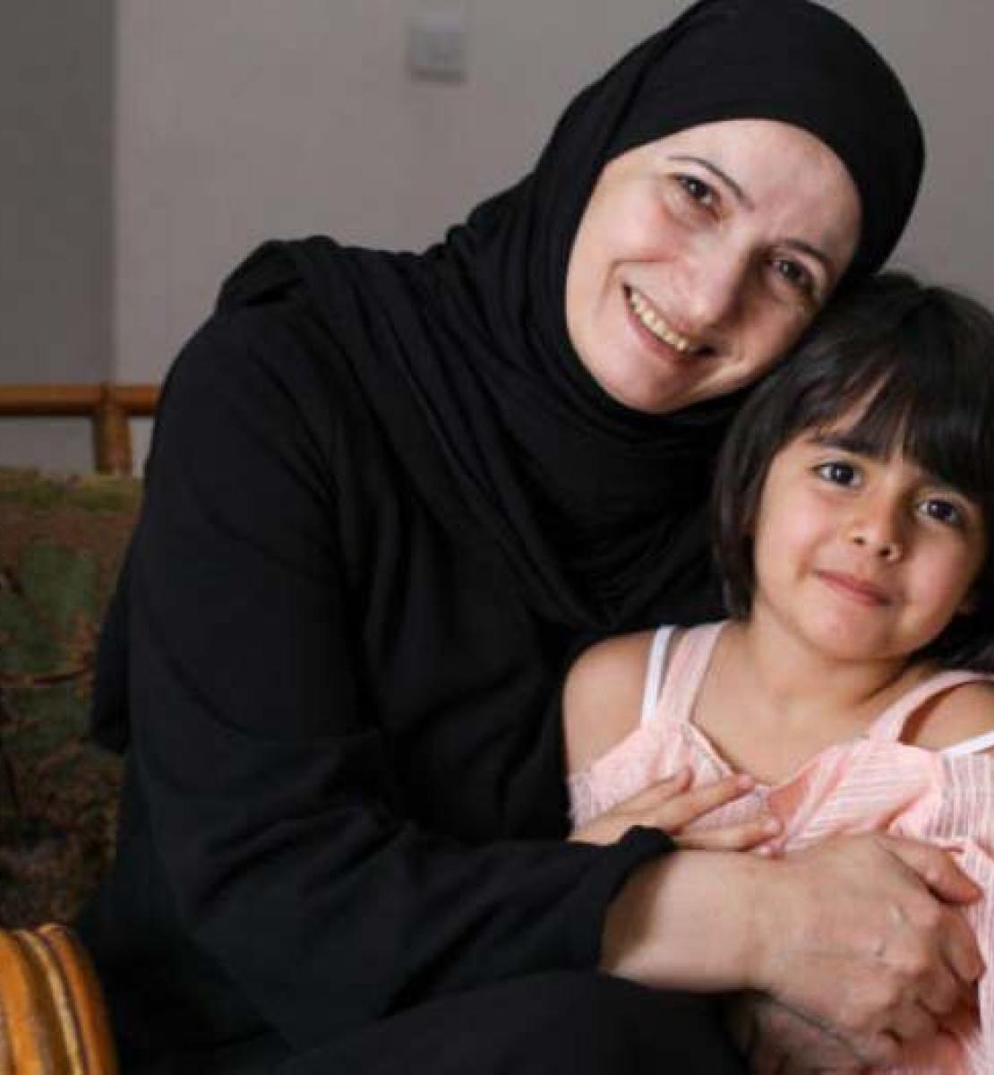 Гада радостно улыбается в камеру, с гордостью обнимая свою младшую дочь, которая также улыбается в камеру.