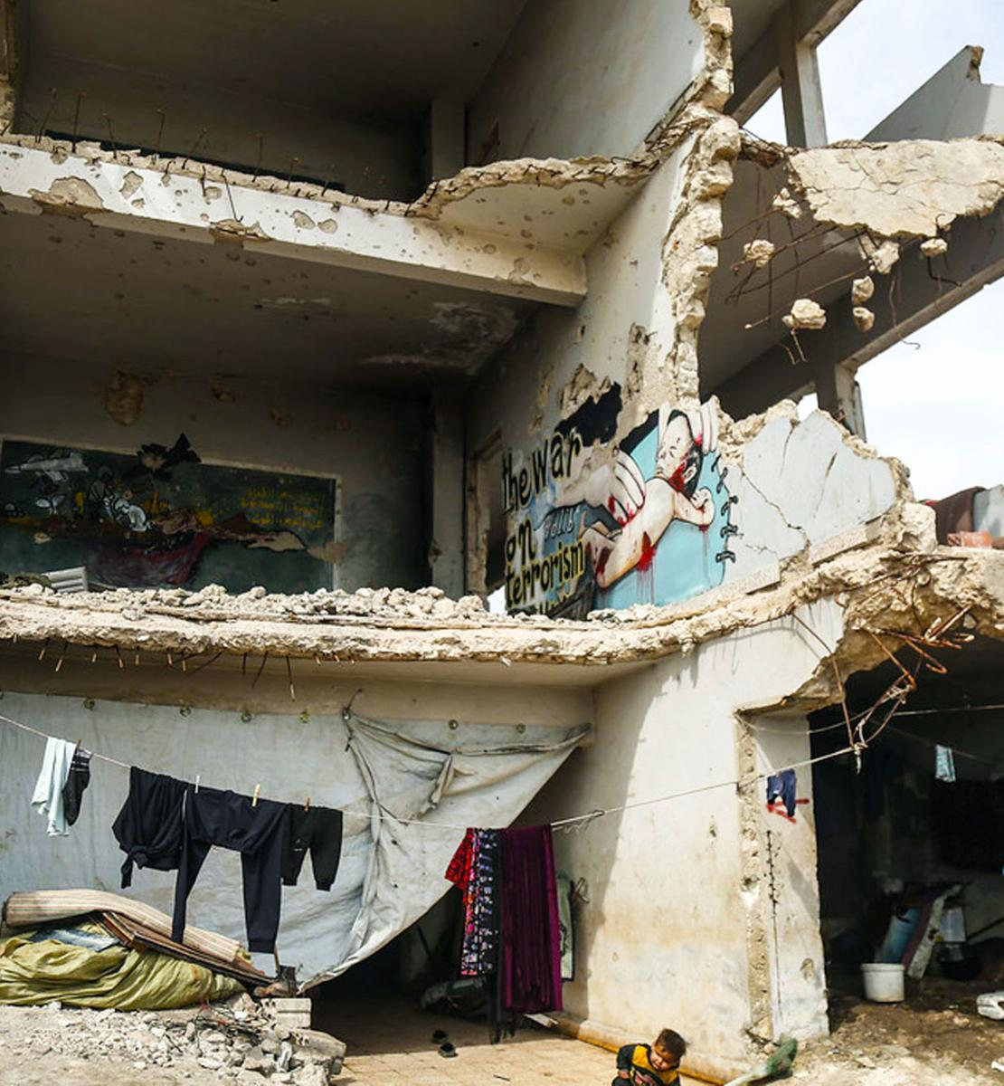 Une femme vêtue d'une robe bleue et portant un enfant dans les bras se tient devant un bâtiment dont la façade a été complètement détruite. Un autre enfant est accroupi près d'elle et une fillette se tient près d'un rebord, au premier étage du bâtiment.
