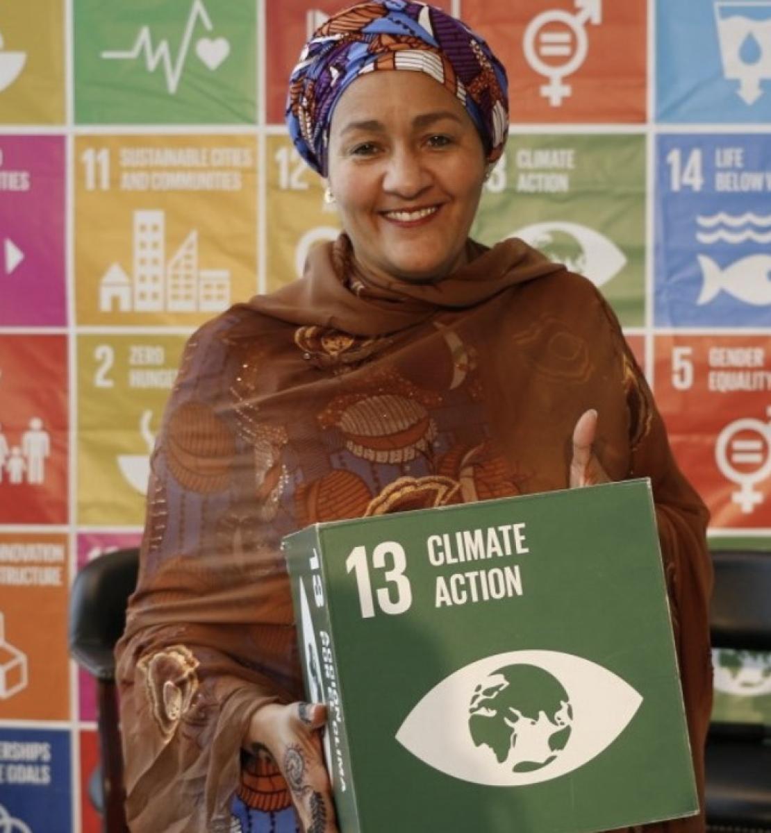 """Amina Mohammed, la Vice-Secrétaire générale de l'ONU, sourit à la caméra en tenant une boîte verte sur laquelle sont inscrits les mots """"Climate Action"""", qui signifient en français """"Action climatique"""". Derrière elle se trouve une grande affiche aux multiples couleurs sur laquelle figurent l'ensemble des ODD."""