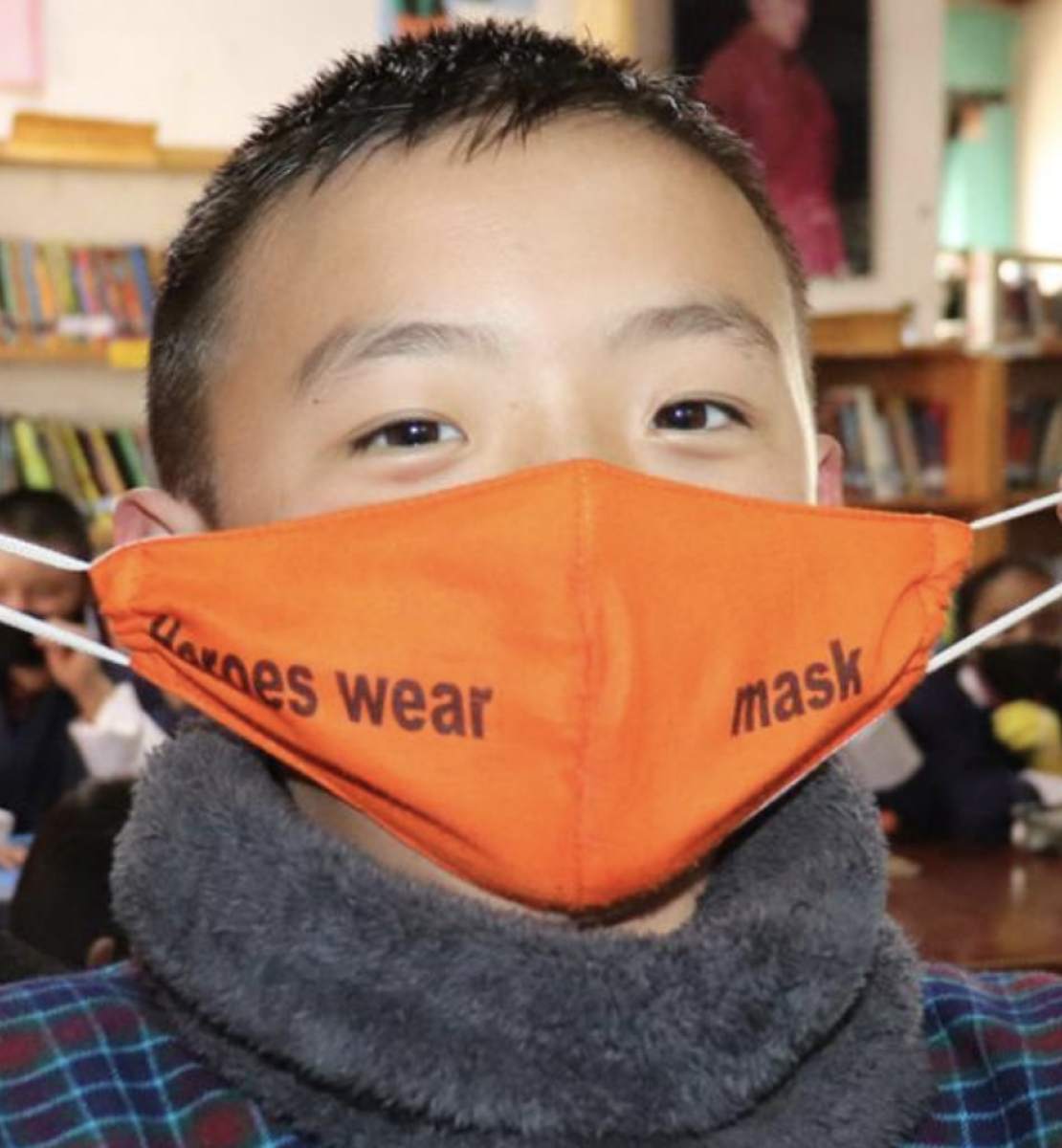 A young boy puts on his orange face mask while looking straight at the camera.