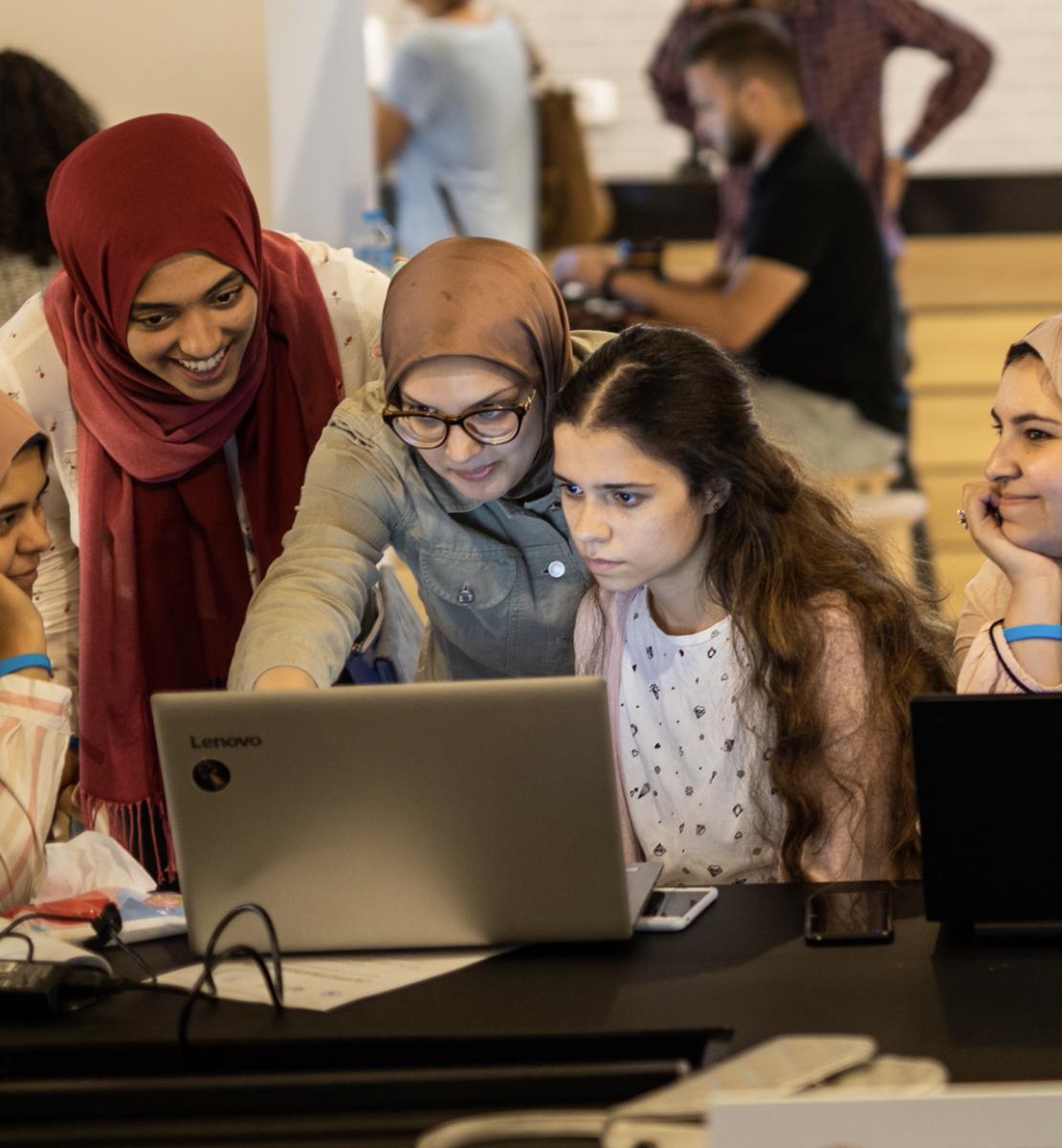 5 jeunes femmes travaillent ensemble sur un écran d'ordinateur portable dans une salle où plusieurs autres personnes consultent des ordinateurs.