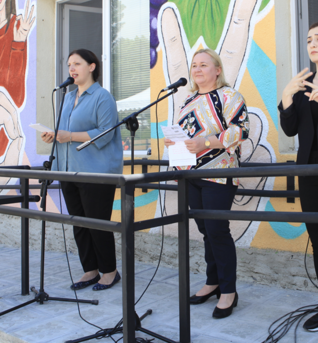 Three women stand in front of a building decorated with many colors. A woman, dressed in black, on the end is translating the speech to sign language.