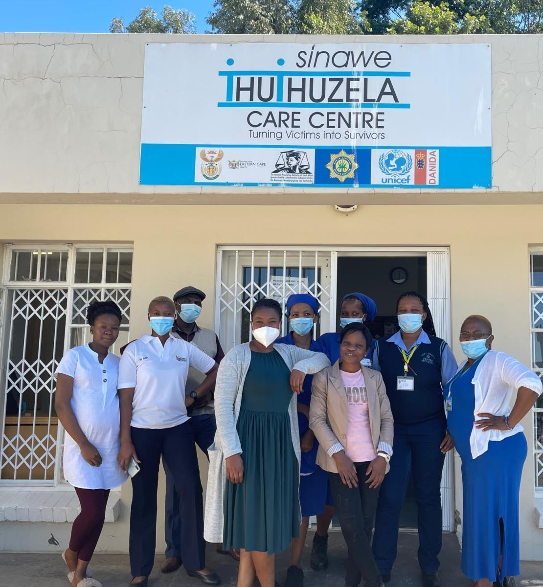 A group of people in face masks stand in front of a white building with a sign hanging above them.